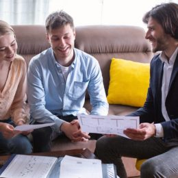 Happy couple with property manager looking at house plan indoors, panorama